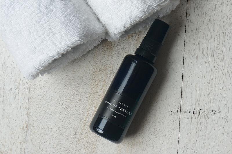 Schwarze Flasche mit Haarstylingprodukt.