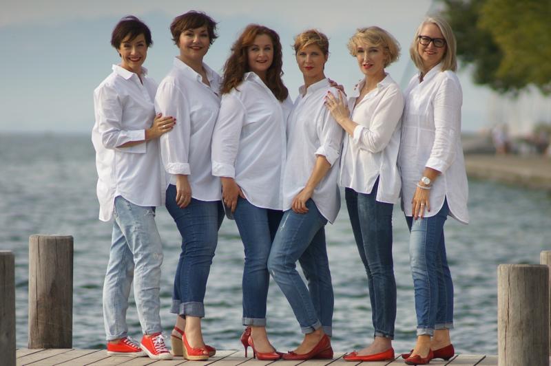 6 Frauen in weißen Blusen, Jeans und roten Schuhen.