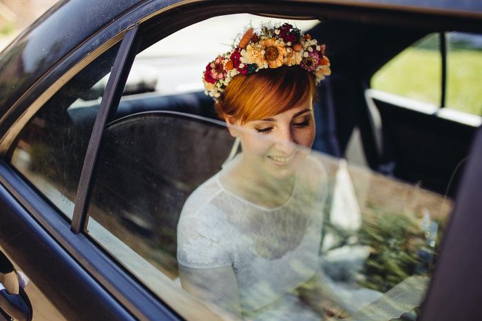 Braut im Auto mit Blumenkranz.
