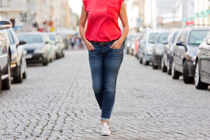 Detailansicht des Outfits mit Jeans und Sneakers.